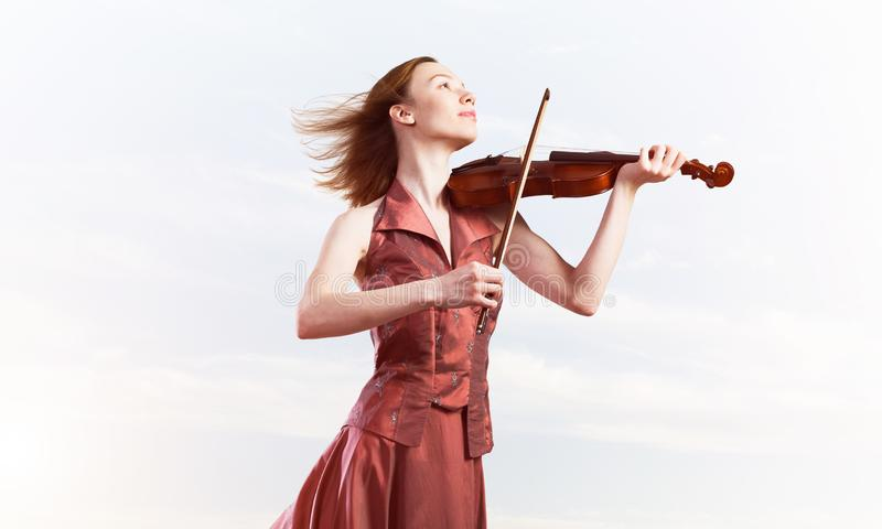 Woman violinist in red dress playing melody against cloudy sky. Young attractive girl playing violin over blue sky and cloud royalty free stock images