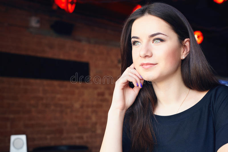 Young attractive girl posing in modern coffee shop royalty free stock photography