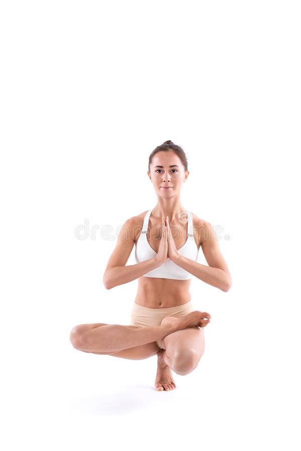 Young attractive girl practicing yoga isolated on white background. Control balance exercise royalty free stock photo