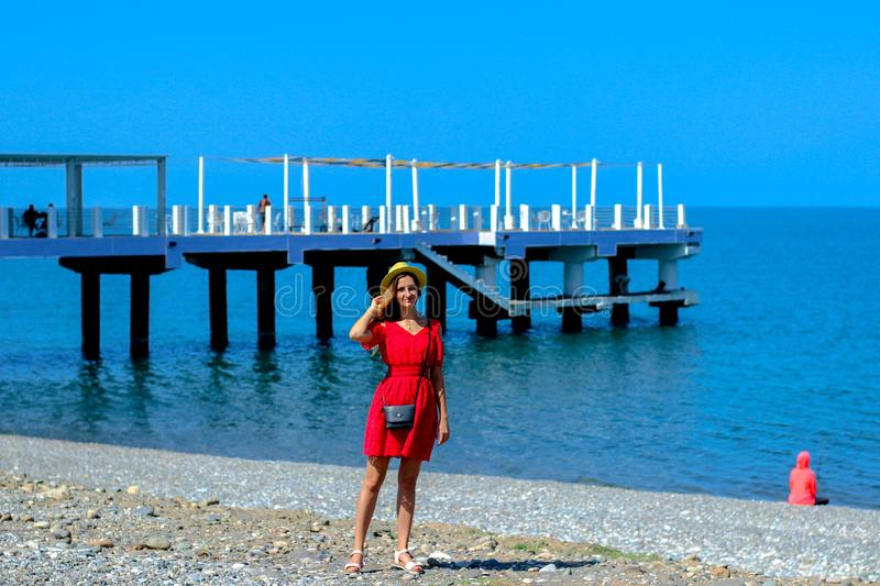 Young attractive girl in a red dress near the sea in the summer, Batumi, Georgia stock photo