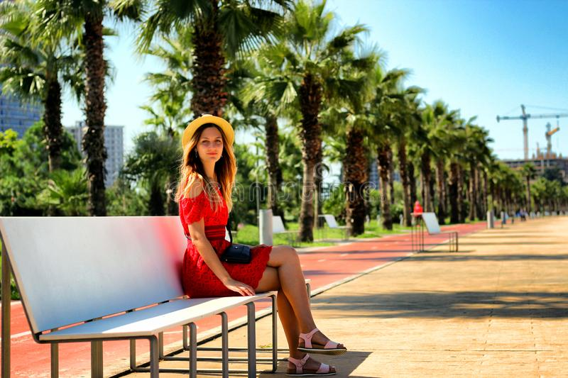 Young attractive girl in a red dress sitting on a bench near the sea in the summer, Batumi, Georgia stock photos