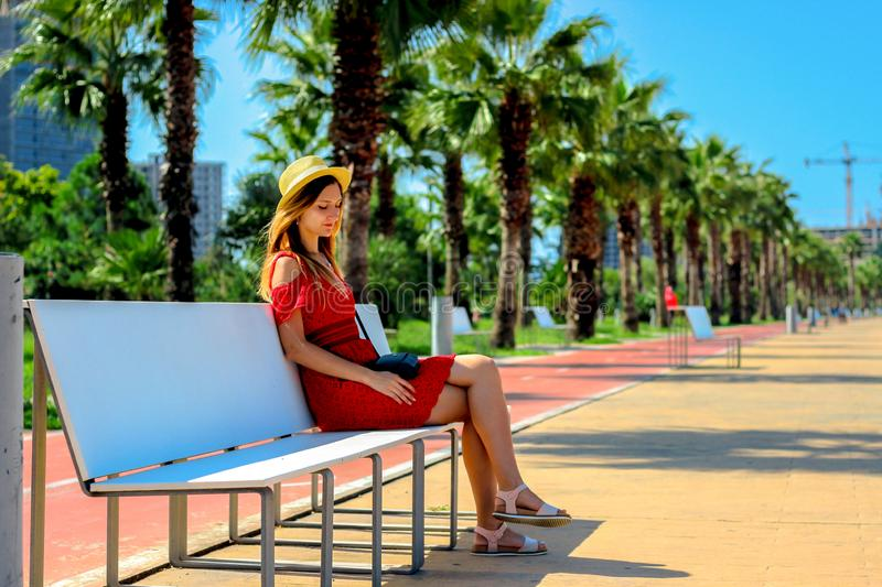 Young attractive girl in a red dress sitting on a bench near the sea in the summer, Batumi, Georgia royalty free stock photos