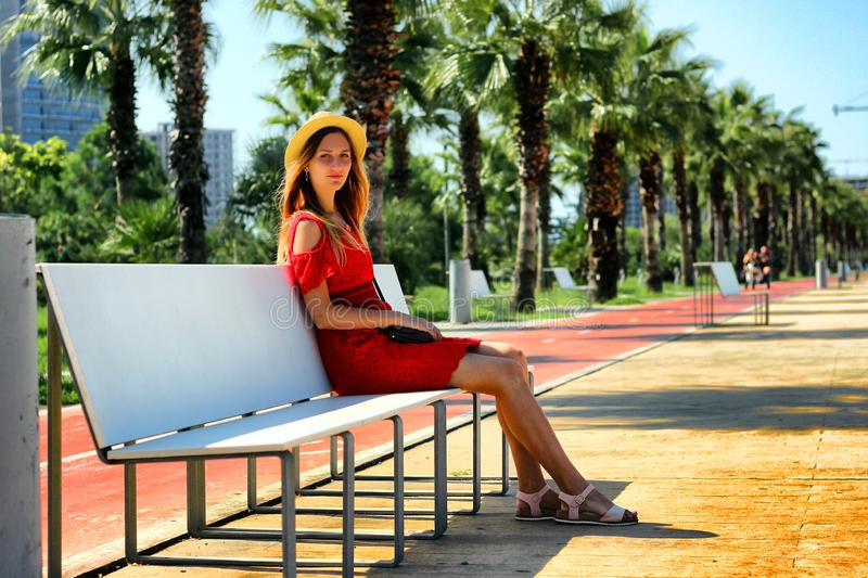 Young attractive girl in a red dress sitting on a bench near the sea in the summer, Batumi, Georgia stock photo