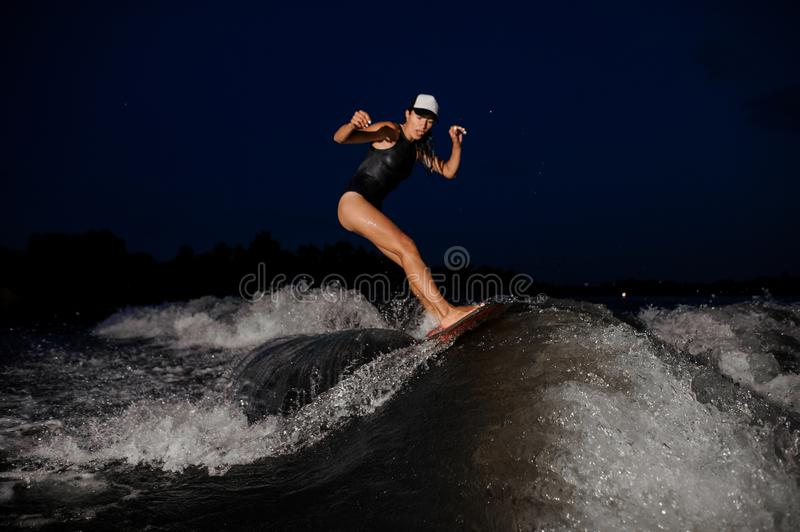 Young attractive girl riding on the orange wakesurf in the night stock photo