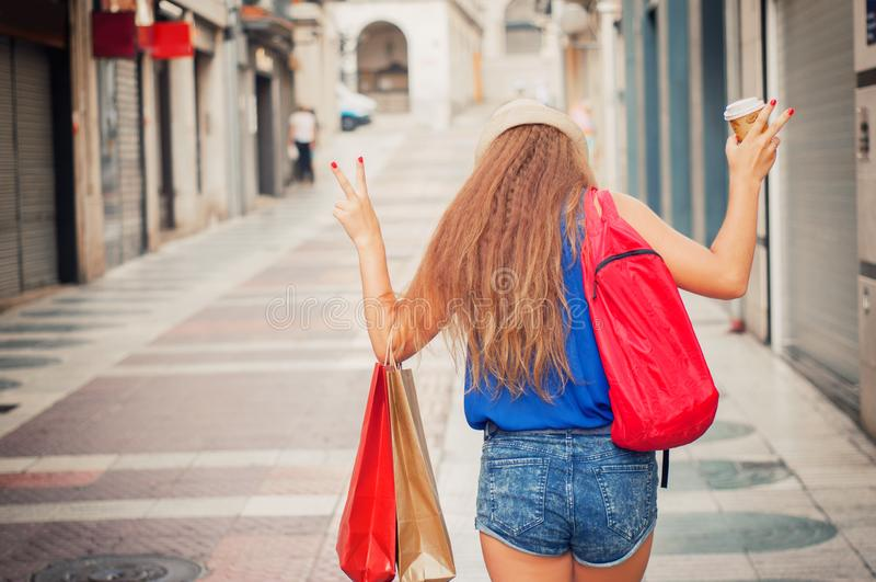 Young attractive girl with shopping bags, backpack and with a pl royalty free stock photo