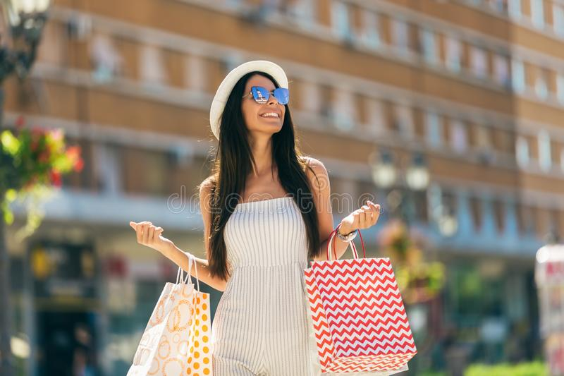 Attractive girl with shopping bags in the city royalty free stock photography