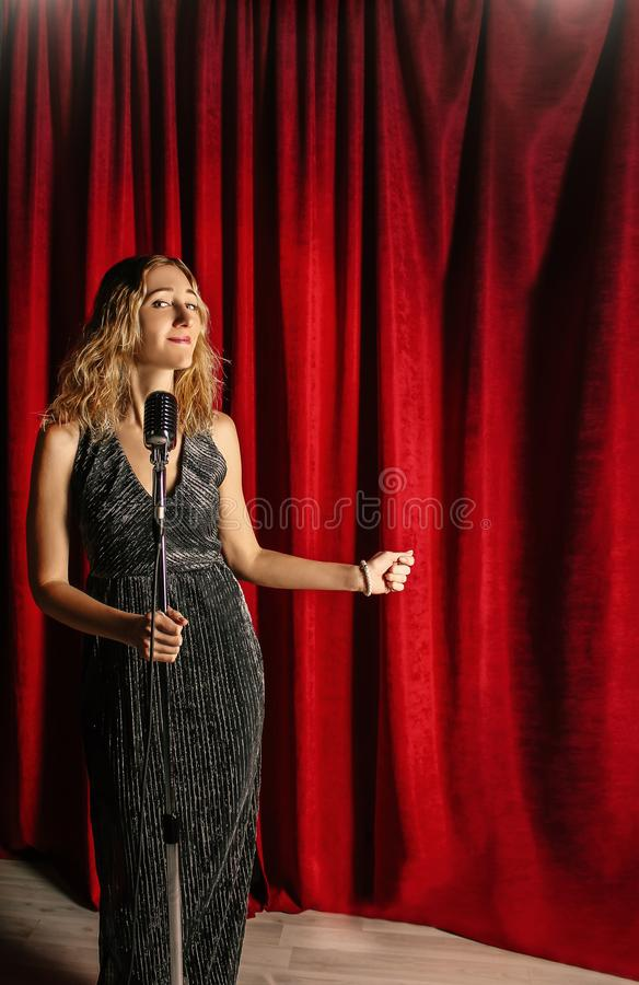 Young attractive girl singing on stage with microphone against t royalty free stock photos