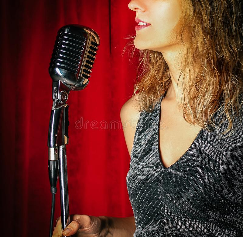 Young attractive girl singing on stage with microphone against t royalty free stock photo