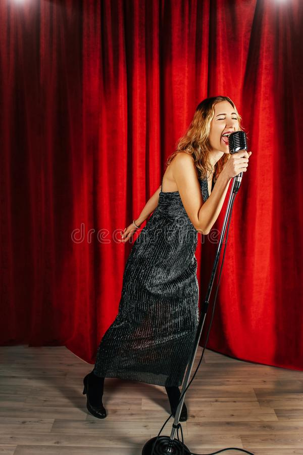 Young attractive girl singing on stage with microphone against t stock images