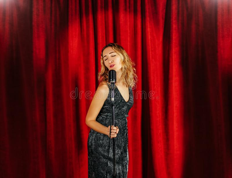 Young attractive girl singing on stage with microphone against t stock image