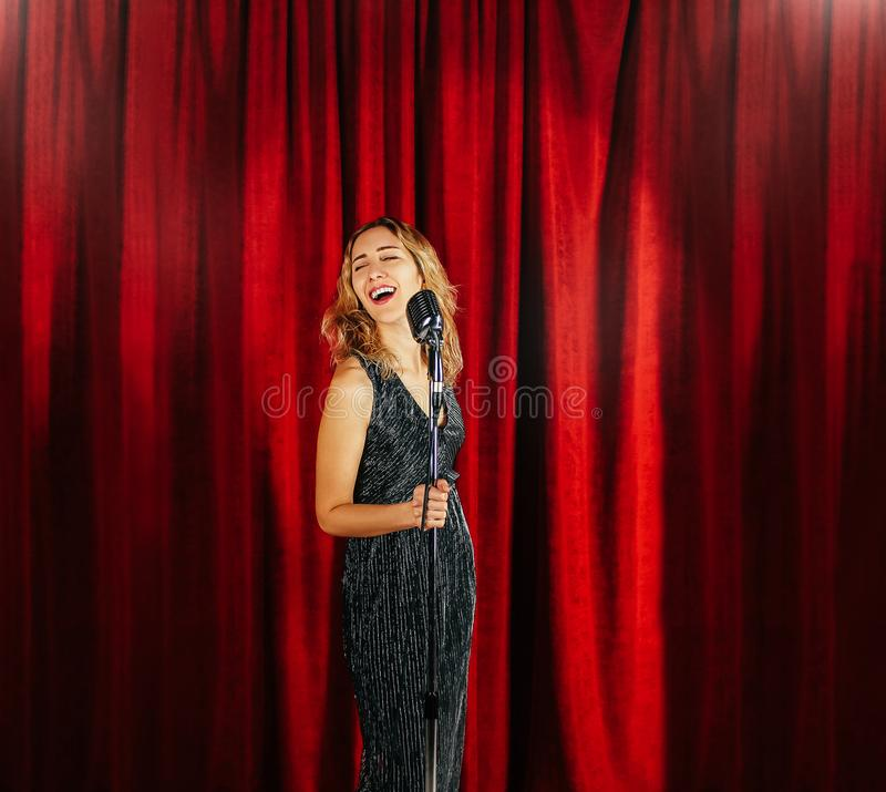 Young attractive girl singing on stage with microphone against t stock photo