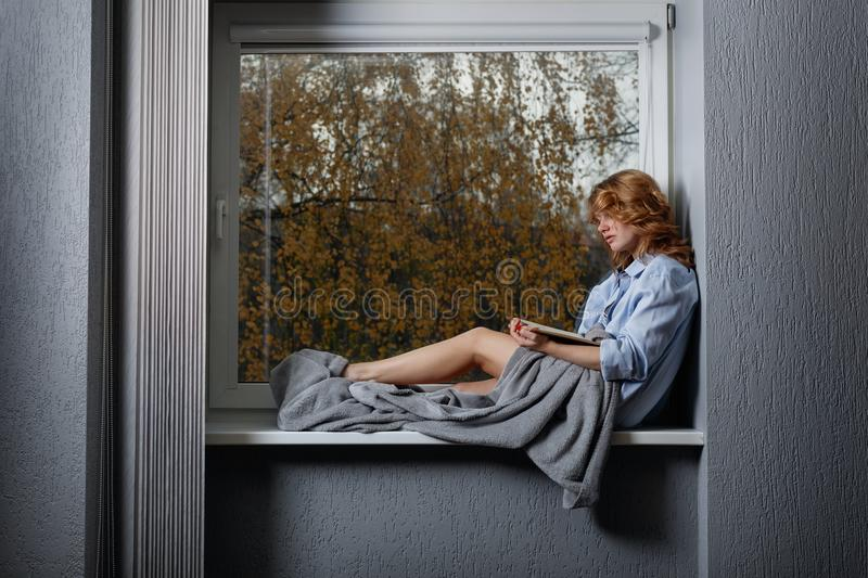 Young attractive girl on the window sill . royalty free stock image