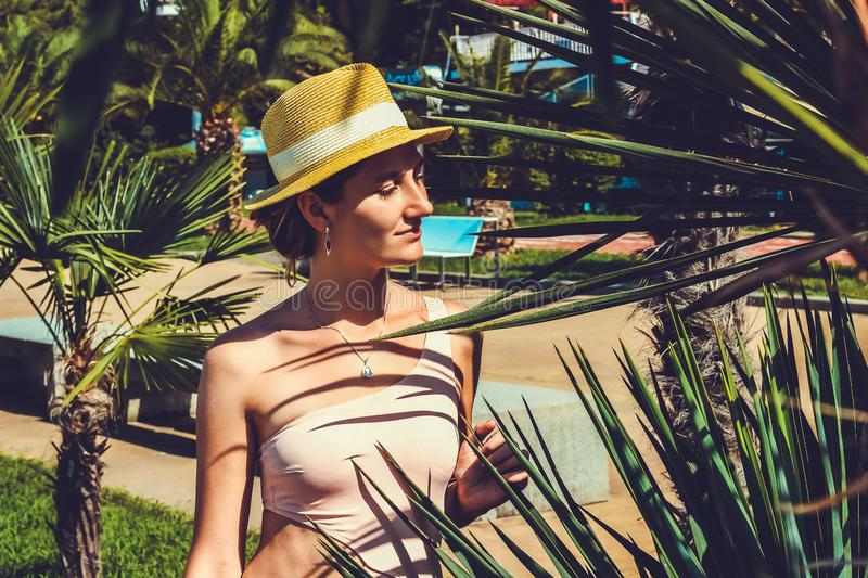 Young attractive girl in a swimsuit close up among palm trees stock image