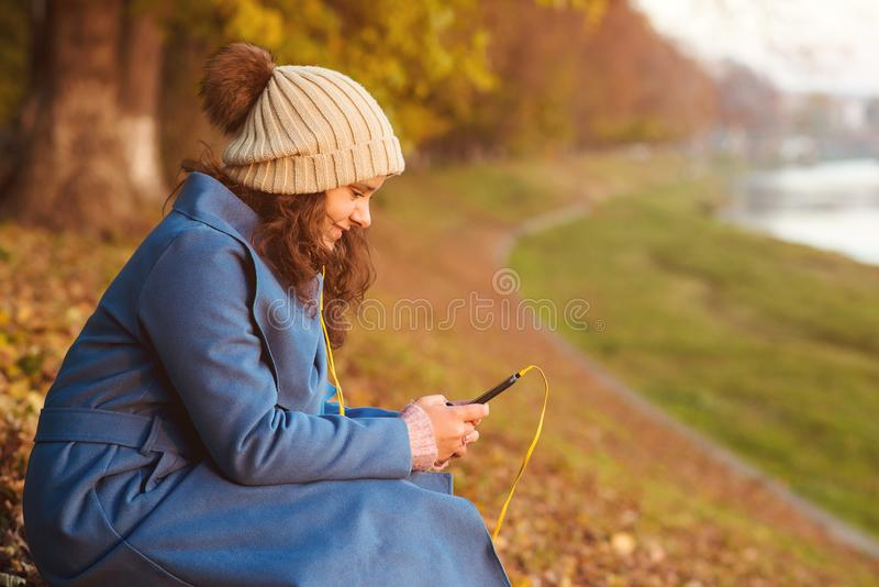 Young attractive girl using smartphone outdoors. Student girl walking in autumn day. Happy brunette woman in autumn clothes enjoyi royalty free stock image