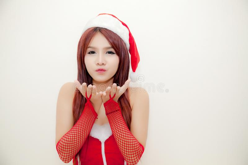 Young attractive girl wear santa suit and santa hat open the palm of two hands and standing on white background. royalty free stock image