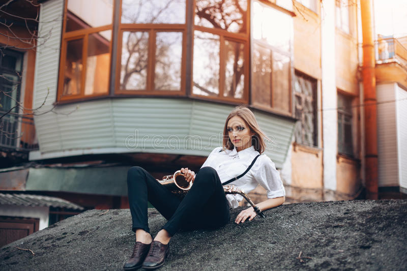 Young attractive girl in white shirt with a saxophone sitting sits on the earth - outdoor. young woman with sax looking at ca. Mera royalty free stock images