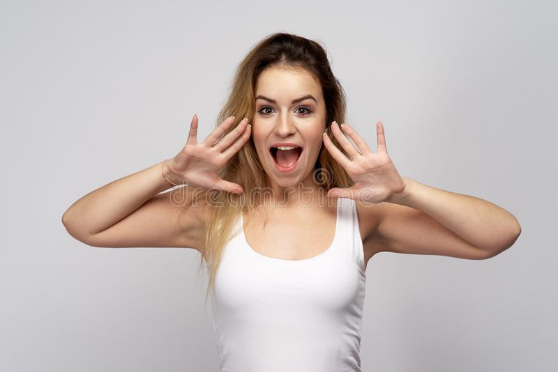 Young attractive girl woman with a positive and emotional state screams yells widely opened her mouth and clasped hands in horn stock photo