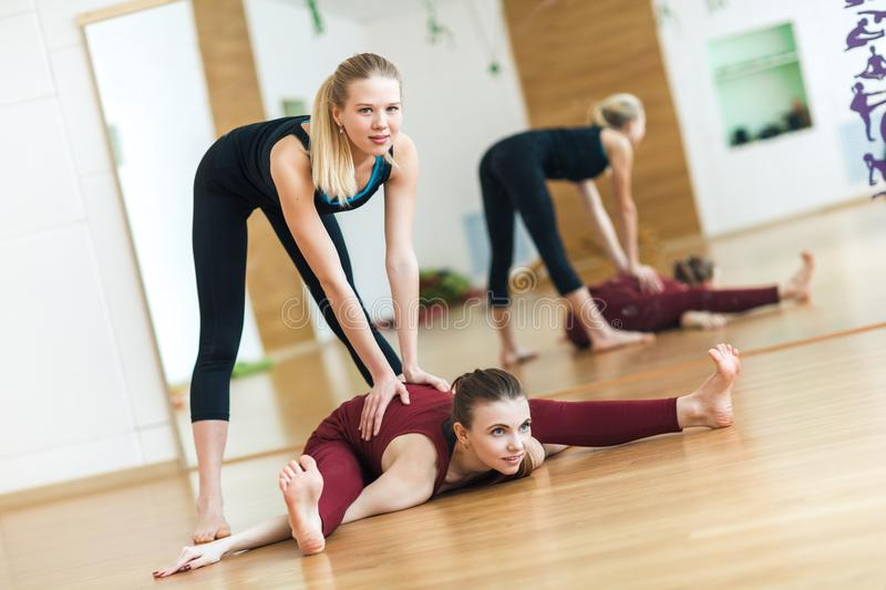 Young, attractive girls help each other to do a stretching exercise while she sits in the split on the floor in the gym. They are royalty free stock photo