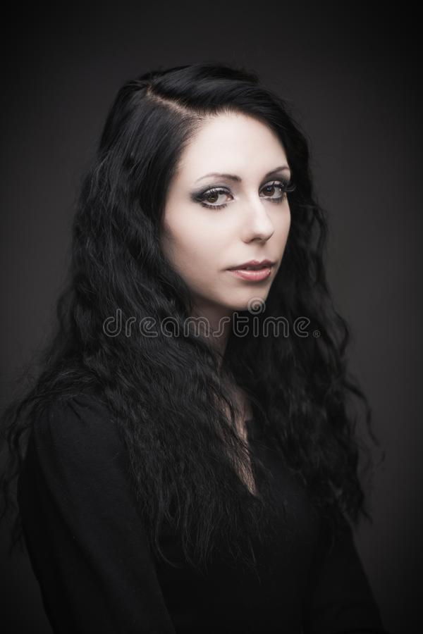 Young attractive gothic brunette woman. Over black royalty free stock photo