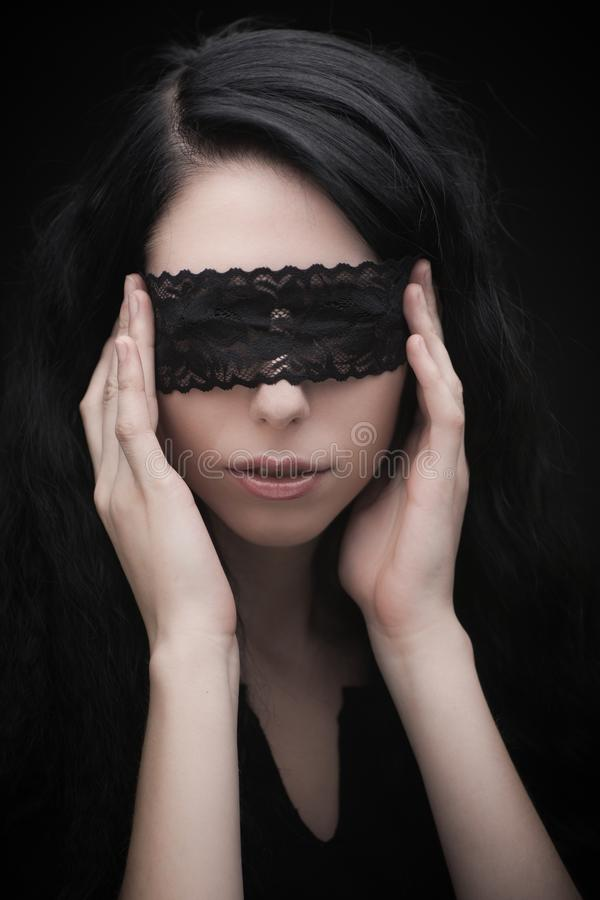 Young attractive gothic brunette woman. Over black with lace strip on eyes stock photos