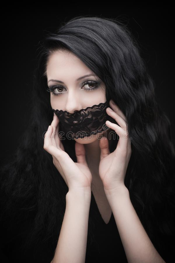 Young attractive gothic brunette woman. Over black with lace strip on lips royalty free stock photo