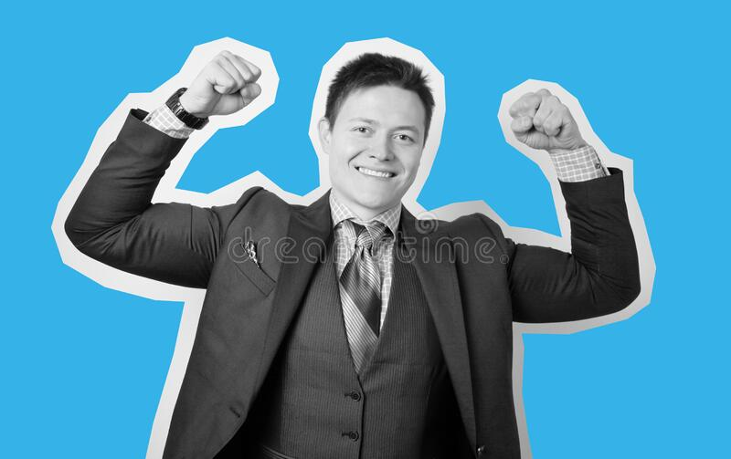 Young attractive guy businessman in suit on gray background with muscular arms, champion and superhero. Success in business.  royalty free stock photography