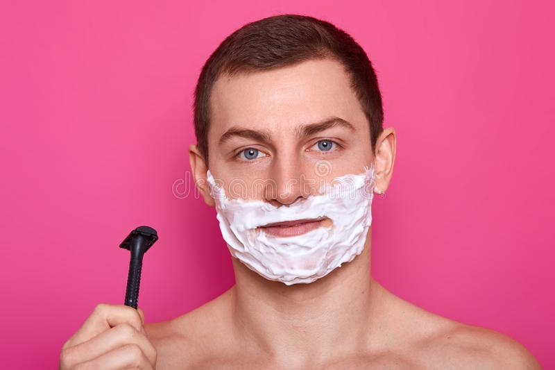 Young attractive guy ready for shaving with razor in bathroom, puts cream on face, over pink background. Handsome man with foam on stock photo
