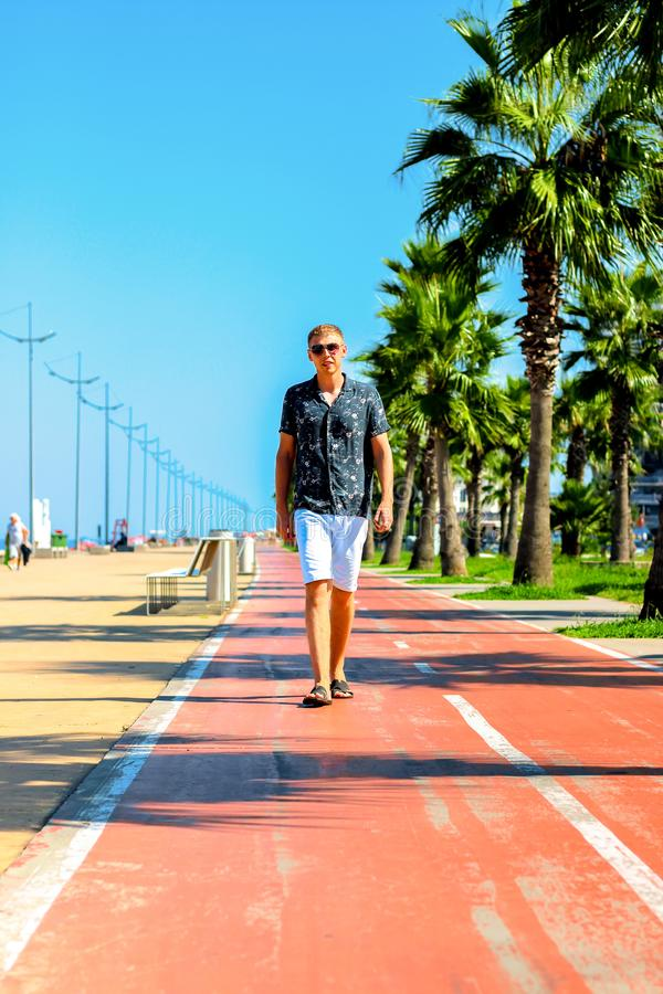 Young attractive guy walks along the pedestrian road with palm trees in the summer, near the Black Sea coast, Batumi, Georgia royalty free stock photography
