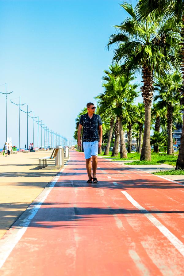 Young attractive guy walks along the pedestrian road with palm trees in the summer, near the Black Sea coast, Batumi, Georgia stock photography