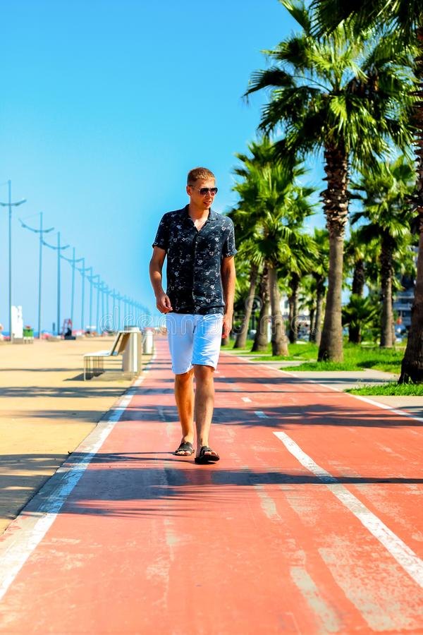 Young attractive guy walks along the pedestrian road with palm trees in the summer, near the Black Sea coast, Batumi, Georgia royalty free stock photo