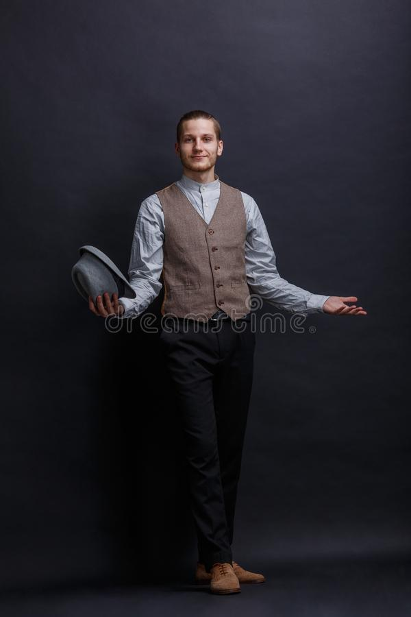 Young attractive guy, wearing a retro suit, stands on a dark background removing his hat and smiling. royalty free stock photography