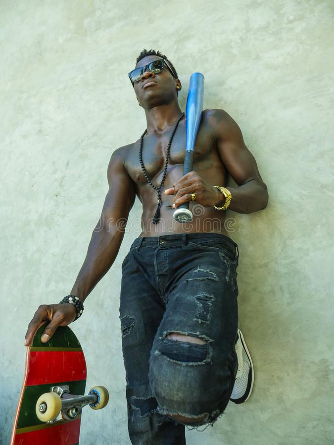 Young attractive and handsome black African American man with fit muscular body and six pack holding baseball bat and skate board stock photos
