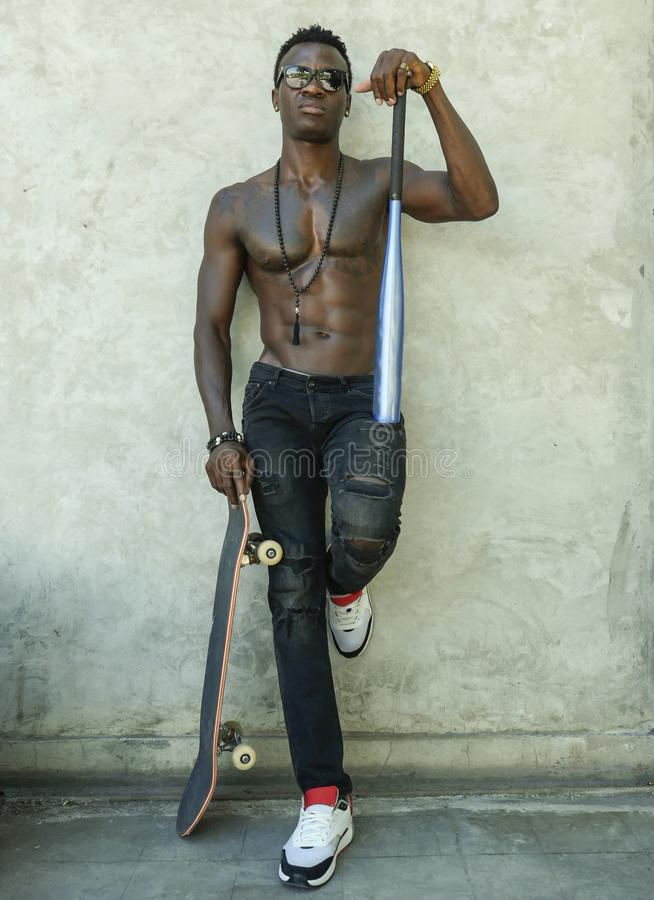 Young attractive and handsome black African American man with fit muscular body and six pack holding baseball bat and skate board royalty free stock image