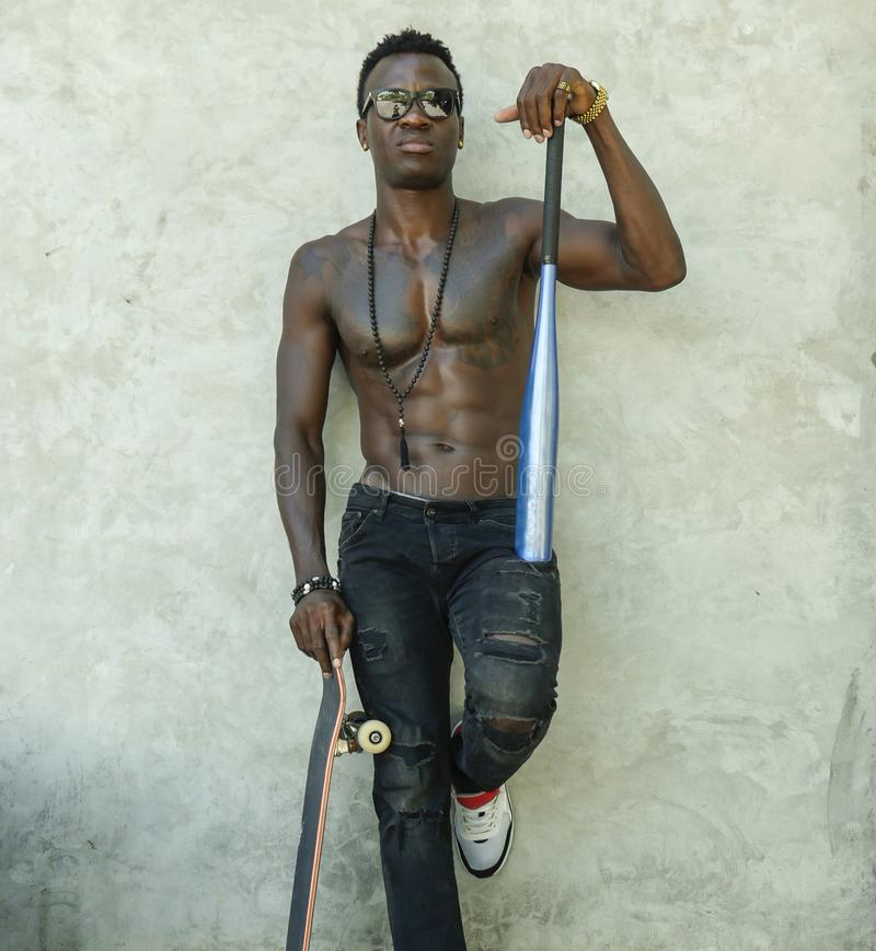 Young attractive and handsome black afro American man with fit muscular body and six pack holding baseball bat and skate board stock photography