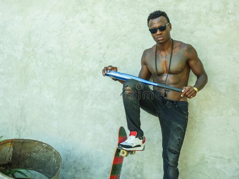 Young attractive and handsome black afro American man with fit muscular body and six pack holding baseball bat and skate board royalty free stock photography