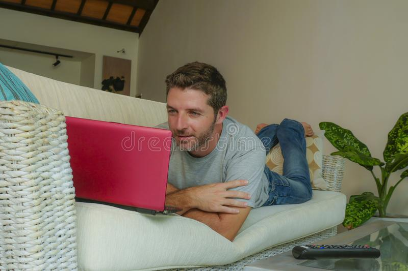 Young attractive handsome happy man lying at home couch working with laptop computer netbook relaxed in internet business concept. Lifestyle indoors portrait of stock photos