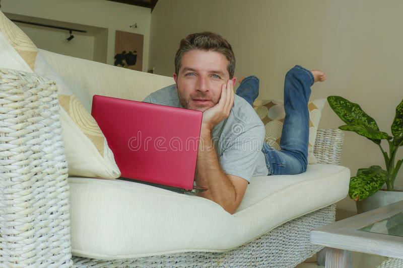 Young attractive and handsome happy man lying at home sofa couch working with laptop computer netbook relaxed in internet business. Lifestyle indoors portrait of stock photo