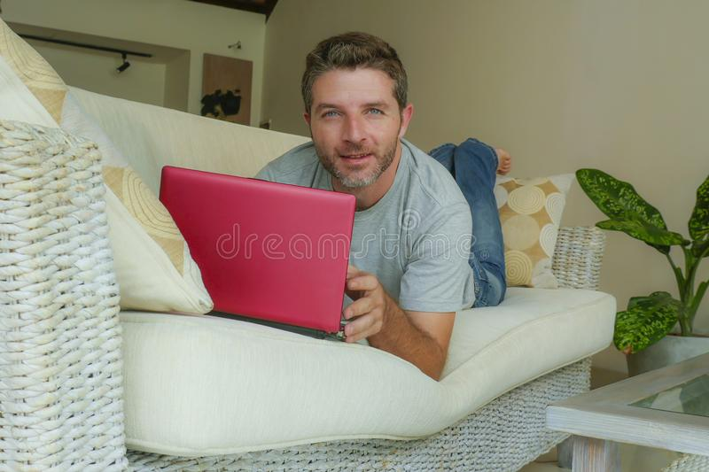 Young attractive and handsome happy man lying at home sofa couch working with laptop computer netbook relaxed in internet business. Lifestyle indoors portrait of royalty free stock images