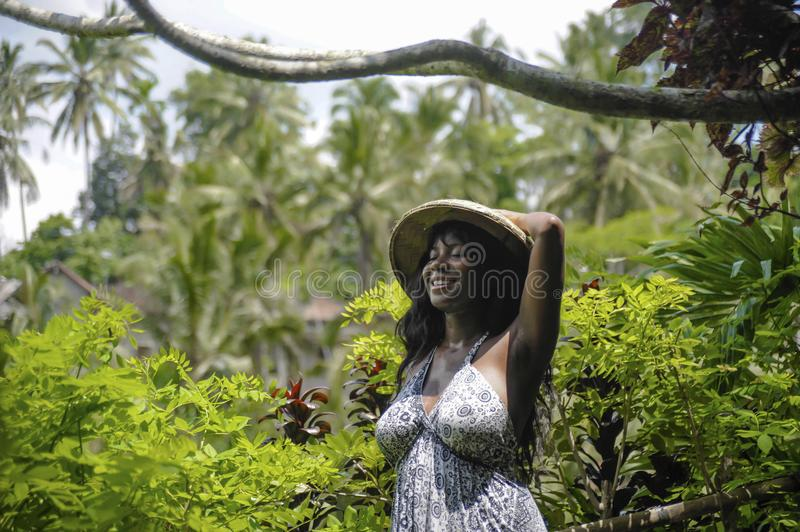 Young attractive happy afro american black woman 30s exploring r. Ice fields forest and jungle in Bali wearing rural traditional Asian hat hiking and exploring stock images