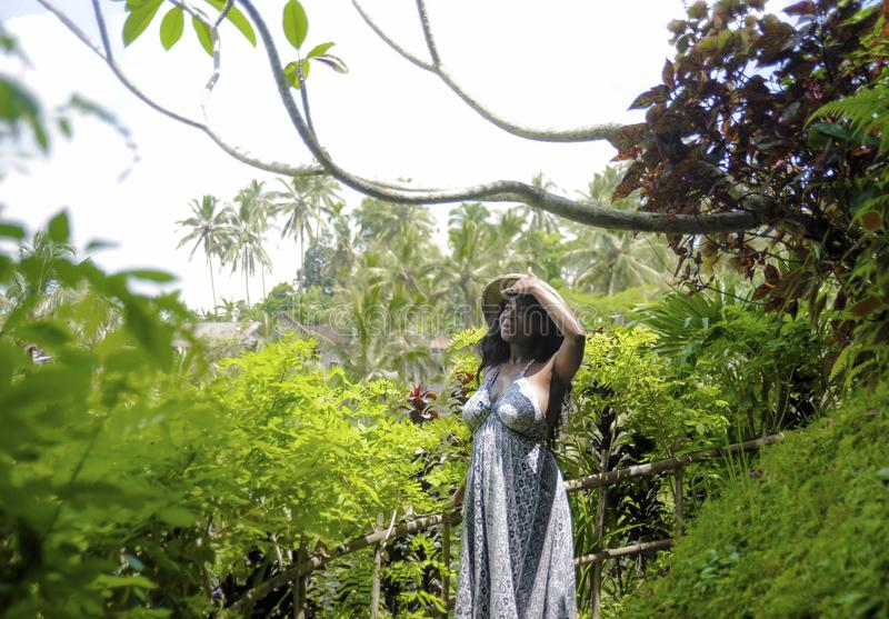 Young attractive happy afro american black woman 30s exploring r. Ice fields forest and jungle in Bali wearing rural traditional Asian hat hiking and exploring royalty free stock photos
