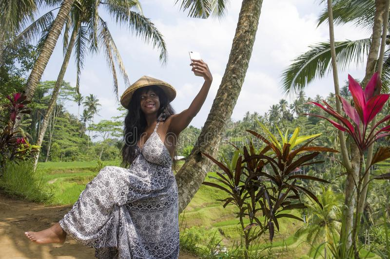 Young attractive happy afro american black woman tourist taking selfie portrait photo with mobile phone camera. While exploring rice fields forest and jungle in royalty free stock images