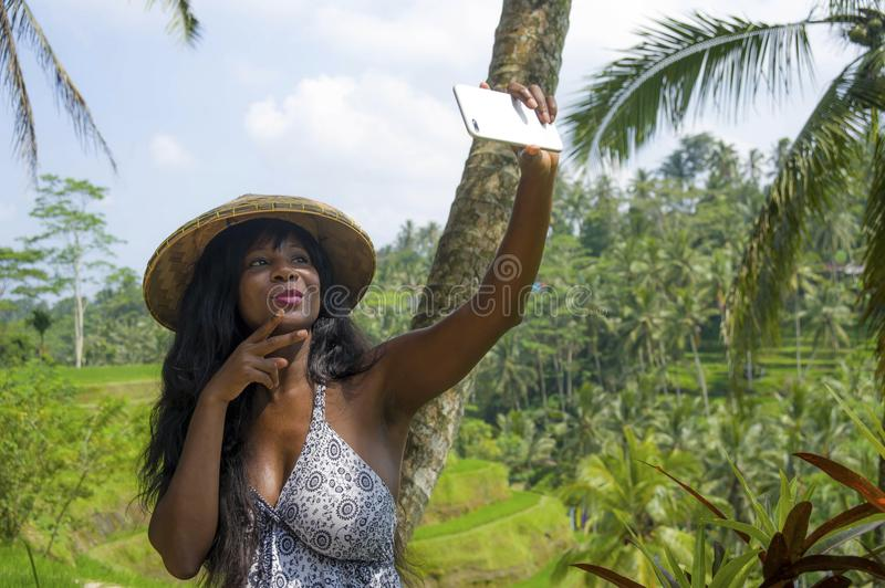Young attractive happy afro american black woman tourist taking selfie portrait photo with mobile phone camera. While exploring rice fields forest and jungle in stock image