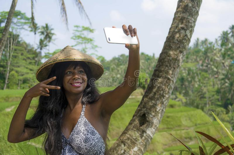 Young attractive happy afro american black woman tourist taking selfie portrait photo with mobile phone camera. While exploring rice fields forest and jungle in stock photo