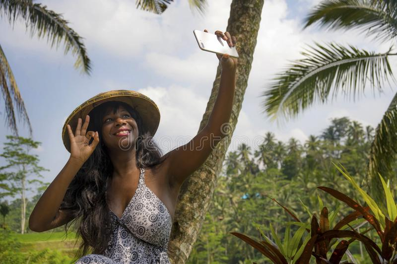 Young attractive happy afro american black woman tourist taking selfie portrait photo with mobile phone camera. While exploring rice fields forest and jungle in royalty free stock photography