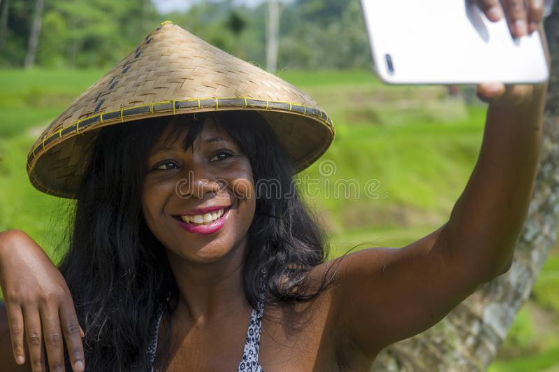 Young attractive happy afro american black woman tourist taking selfie portrait photo with mobile phone camera. While exploring rice fields forest and jungle in royalty free stock image