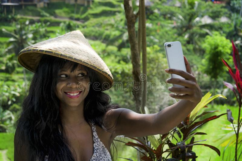 Young attractive happy afro american black woman tourist taking selfie portrait photo with mobile phone camera. While exploring rice fields forest and jungle in royalty free stock photo