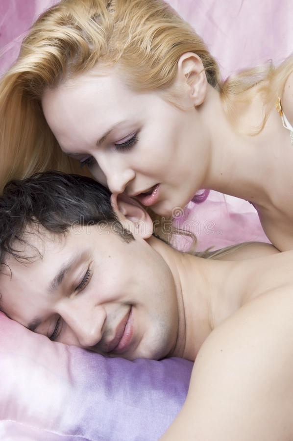 Young attractive happy amorous couple in bed royalty free stock image