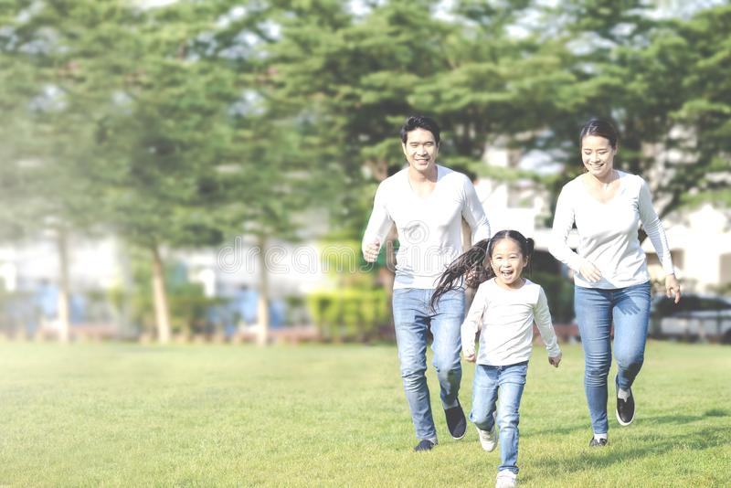 Young attractive happy asian family playing by running together in outside nature park in home school learning or montessori royalty free stock image