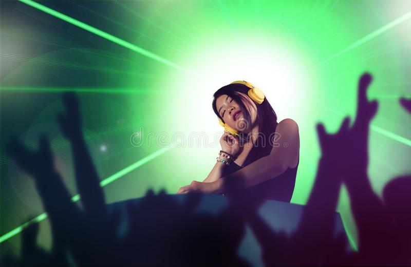 Young attractive and happy Asian Japanese DJ woman remixing using deejay gear and headphones at night club with lights background. Youth and party lifestyle stock photo