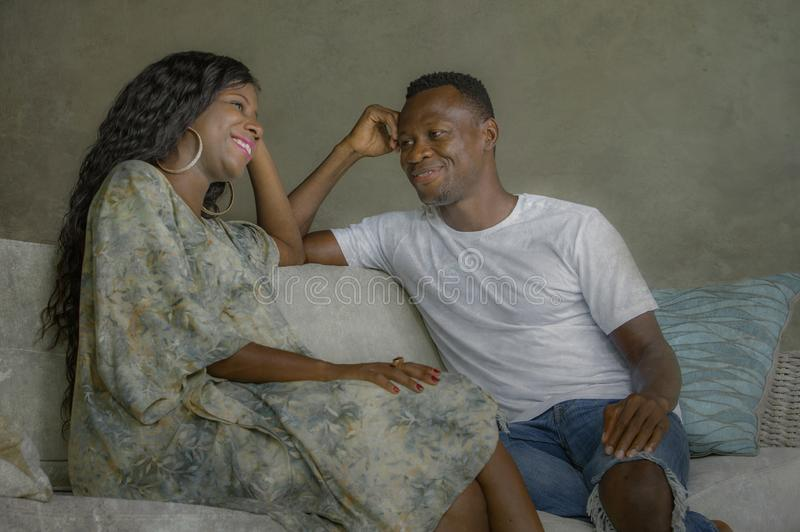 Young attractive and happy black African American couple relaxed at home sofa couch talking sweet enjoying together and smiling in. Men and women in love royalty free stock photo